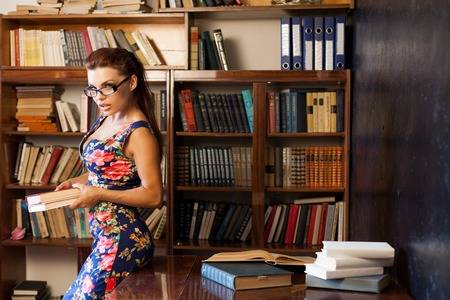 86667701-woman-librarian-in-glasses-sitting-at-the-table-studying-book
